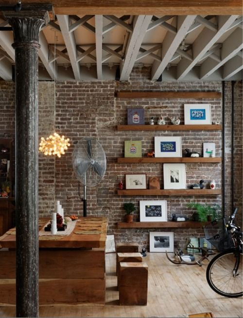 Exposed beams. Shelving on brick wall. Could be an awesome living room or library combination.