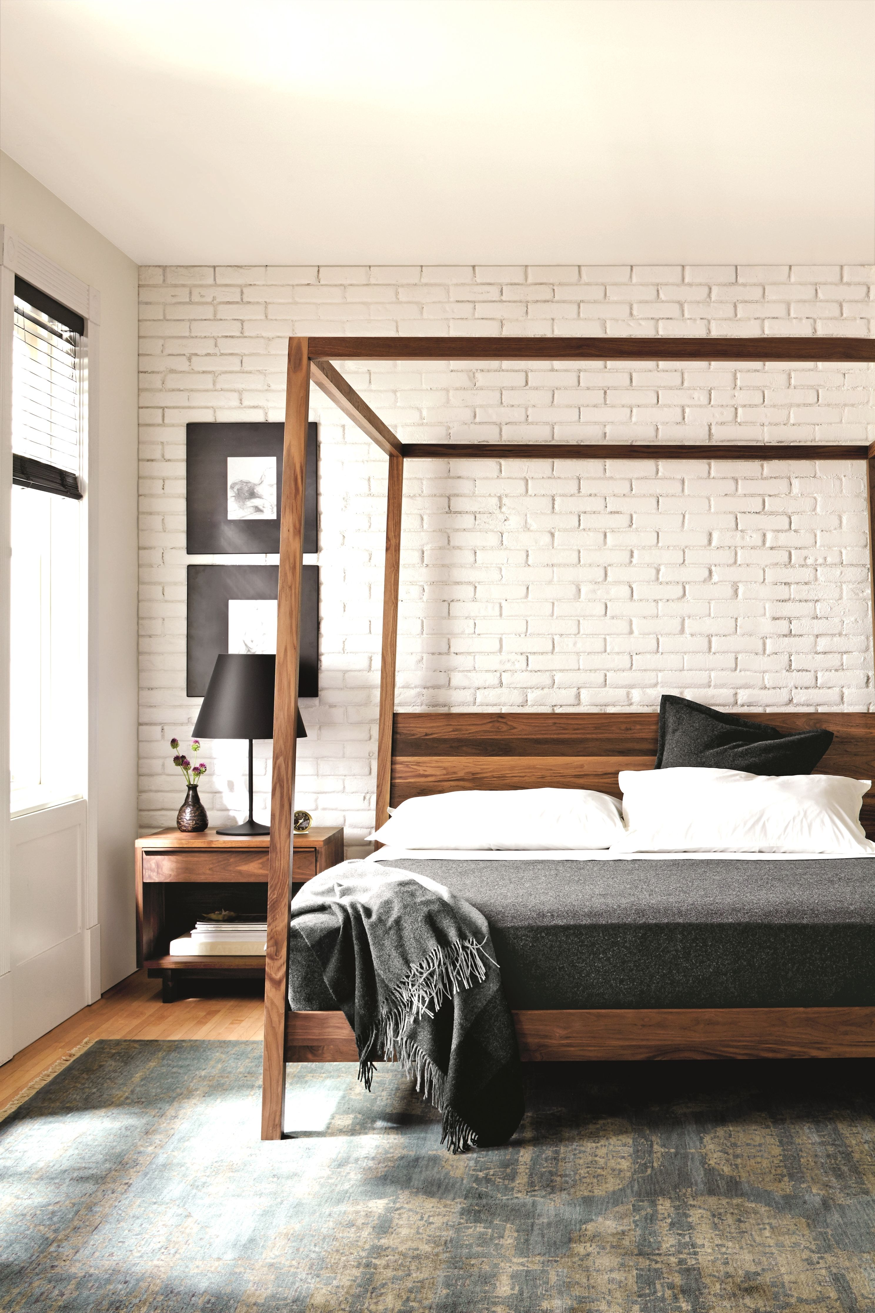 White washed brick plements a minimal wooden bed frame in this sleek simple space BedFrame