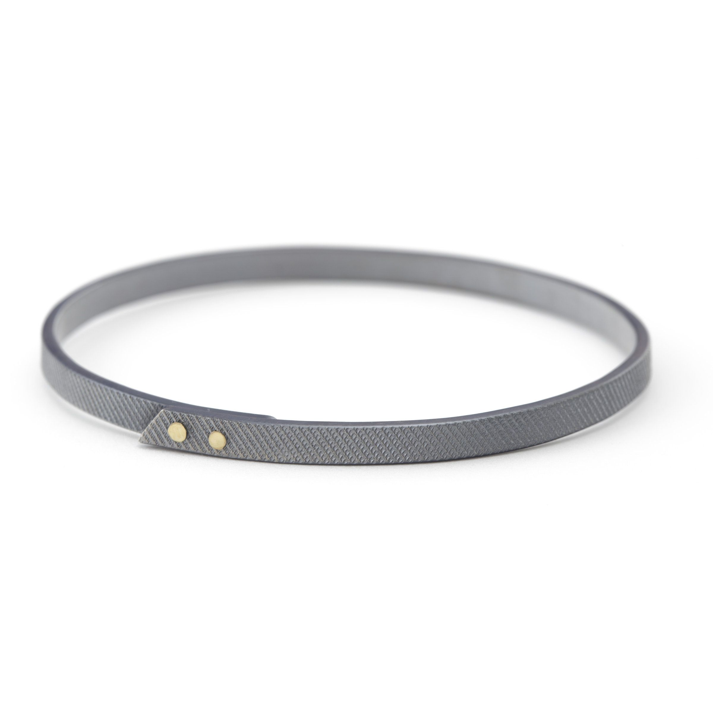 Riveted Gold Bangle by Kendra Renee. A textured band of oxidized sterling silver is accented with two 14K gold rivets for a sleek design with an industrial edge.