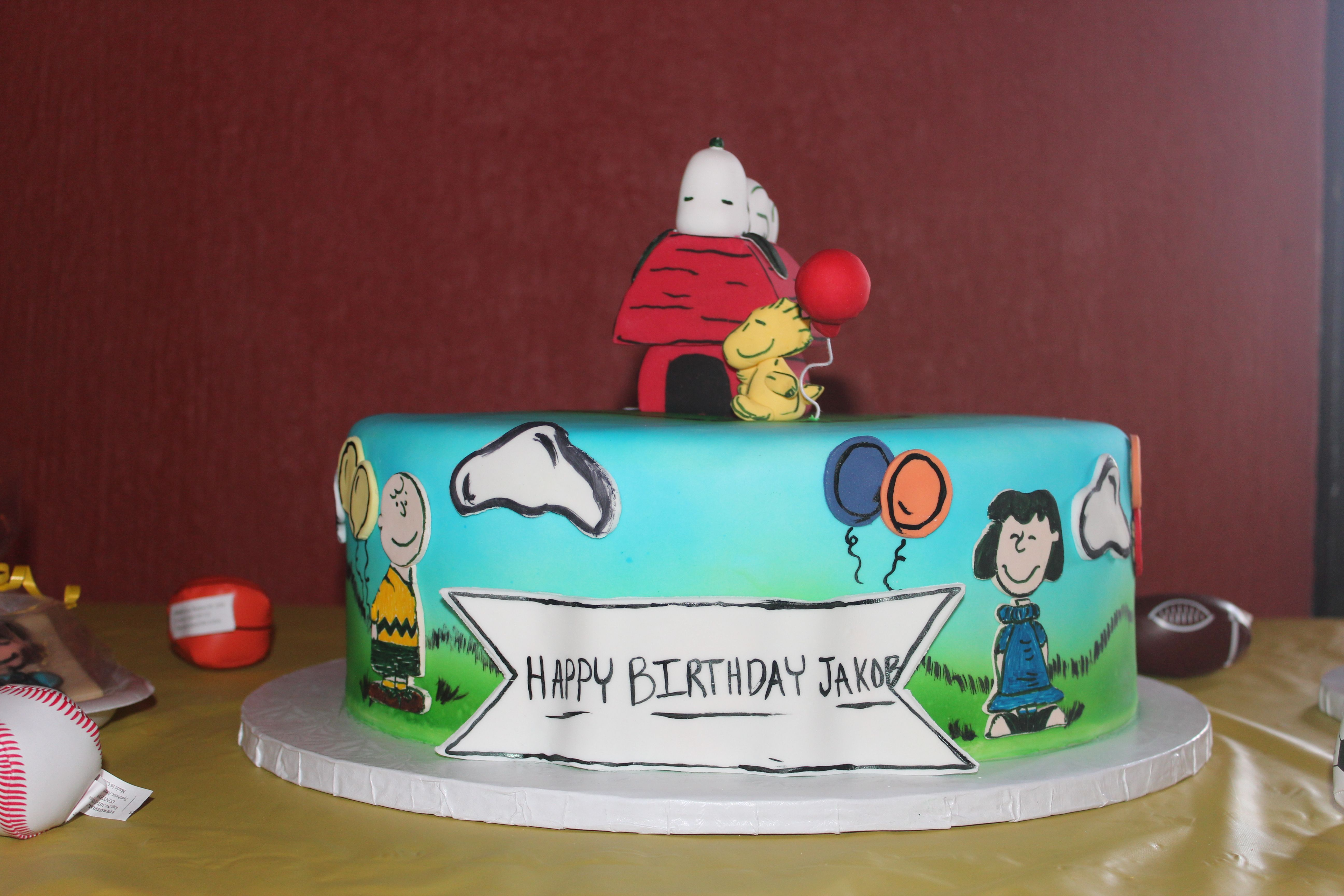 Peanuts characters danced around the cake with Snoopy and Woodstock