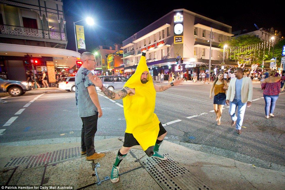 A man in a banana costume is seen with his arms splayed out as he stands on a street curb . & Christmas spirits are high as revellers spill out onto the streets ...
