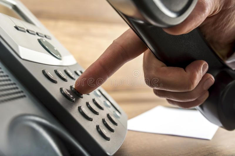 Closeup of male hand dialing a telephone number on black