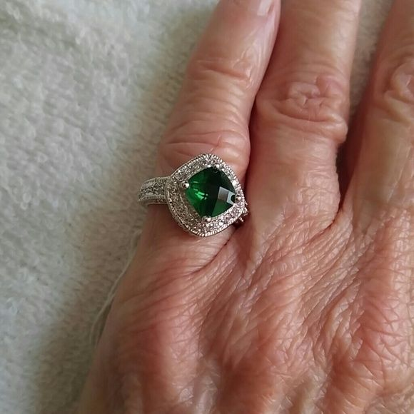 Size 5 Costume Jewelry Ring Beautiful Emerald gemstone surrounded by clear gemstones and continuing down each side. This is a size 5 set in stamped 925 Sterling Silver band. Gorgeous cocktail ring. Jewelry Rings