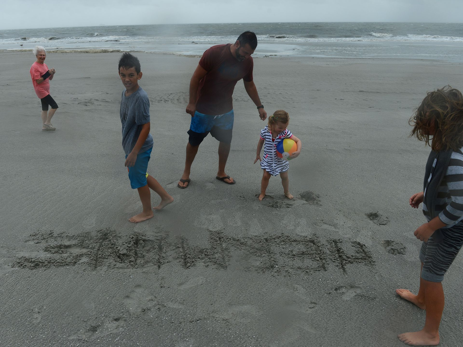 Alex Caro, center, of #VirginiaBeach  He wrote #Hermine in the sand