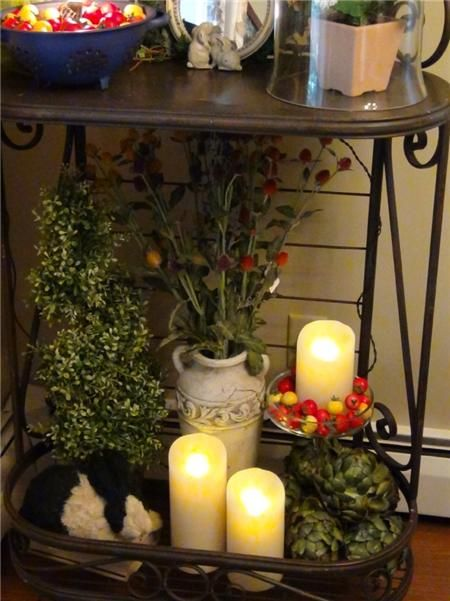 Decorating idea metal baker's rack filled with fake vegetable and fruit, lighted grapes, rabbit basket, topiary, luminara flameless candles