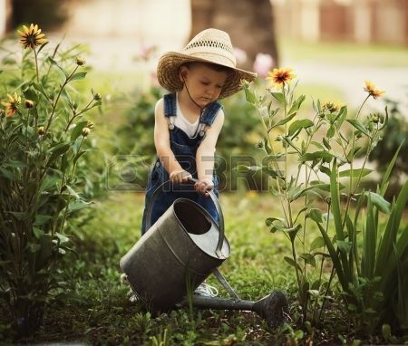 Cute little boy riego flores regadera photos for Jardineria al aire libre casa pendiente