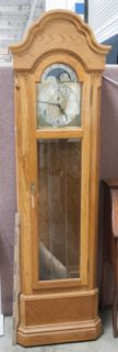EXQUISITE EMPEROR GRANDFATHER CLOCK MADE IN WEST GERMANY. SOLID OAK WITH BRASS AND SILVER TONE ACCENTS AND PENDULUM. MEASURES 23X12X82. THE GLASS LOCKING DOOR IS BEVELED AND INCLUDES THE KEY. MODEL NUMBER UW031098.