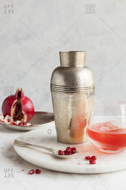 cocktail shaker and pomegranate cocktail on a marble lazy susan