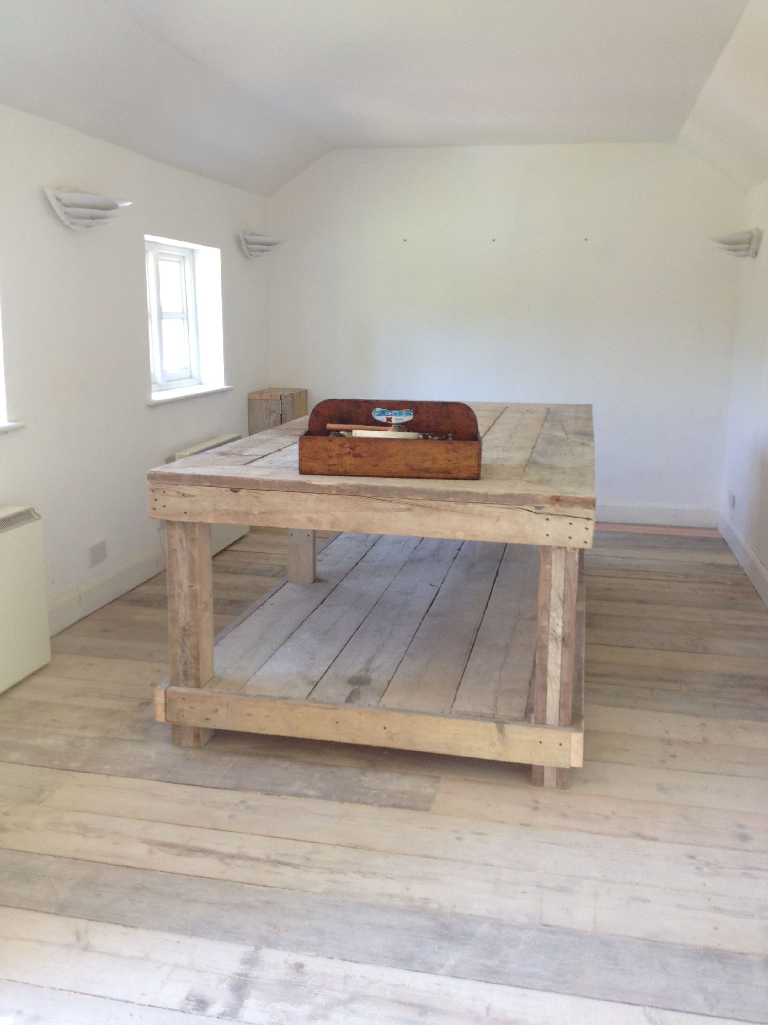 the upholstery studio table and floor are made from reclaimed scaffold