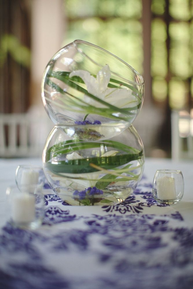 Fishbowl as a centerpiece. Nice for minimal flowers but big impact, optional printed linens to incorporate a 2nd color
