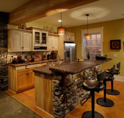 Ackerly Park ~ New Albany, Ohio  http://www.weavercustomhomes.com  Rustic Lower Level Kitchen  Cabinets by Mullet Cabinets, Inc  with an acid stained concrete countertop.    [I love the bar/counter with the stone work!]