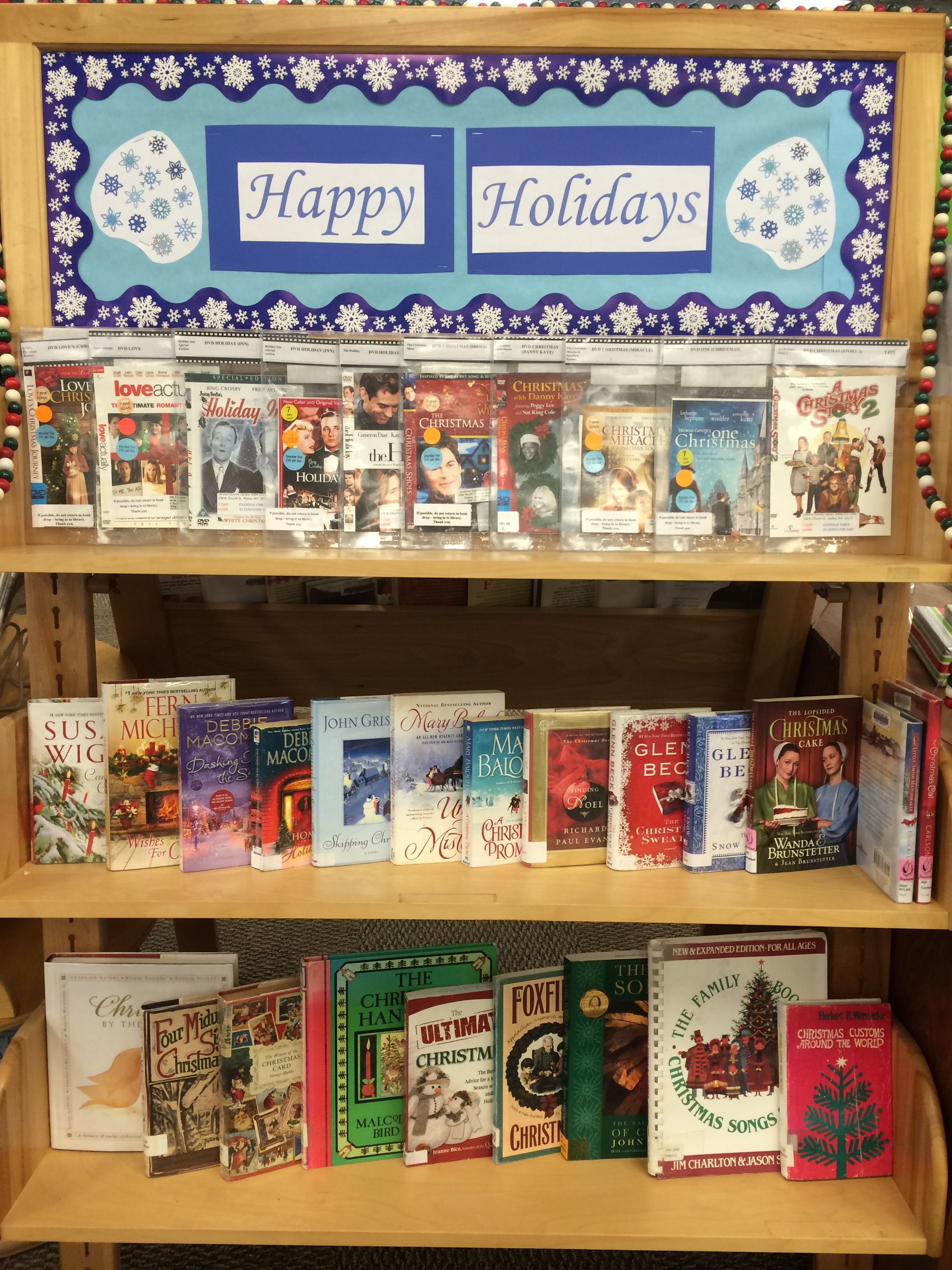 Happy Holidays library display. DVDs on top shelf, fiction in the middle, non-fiction on the bottom