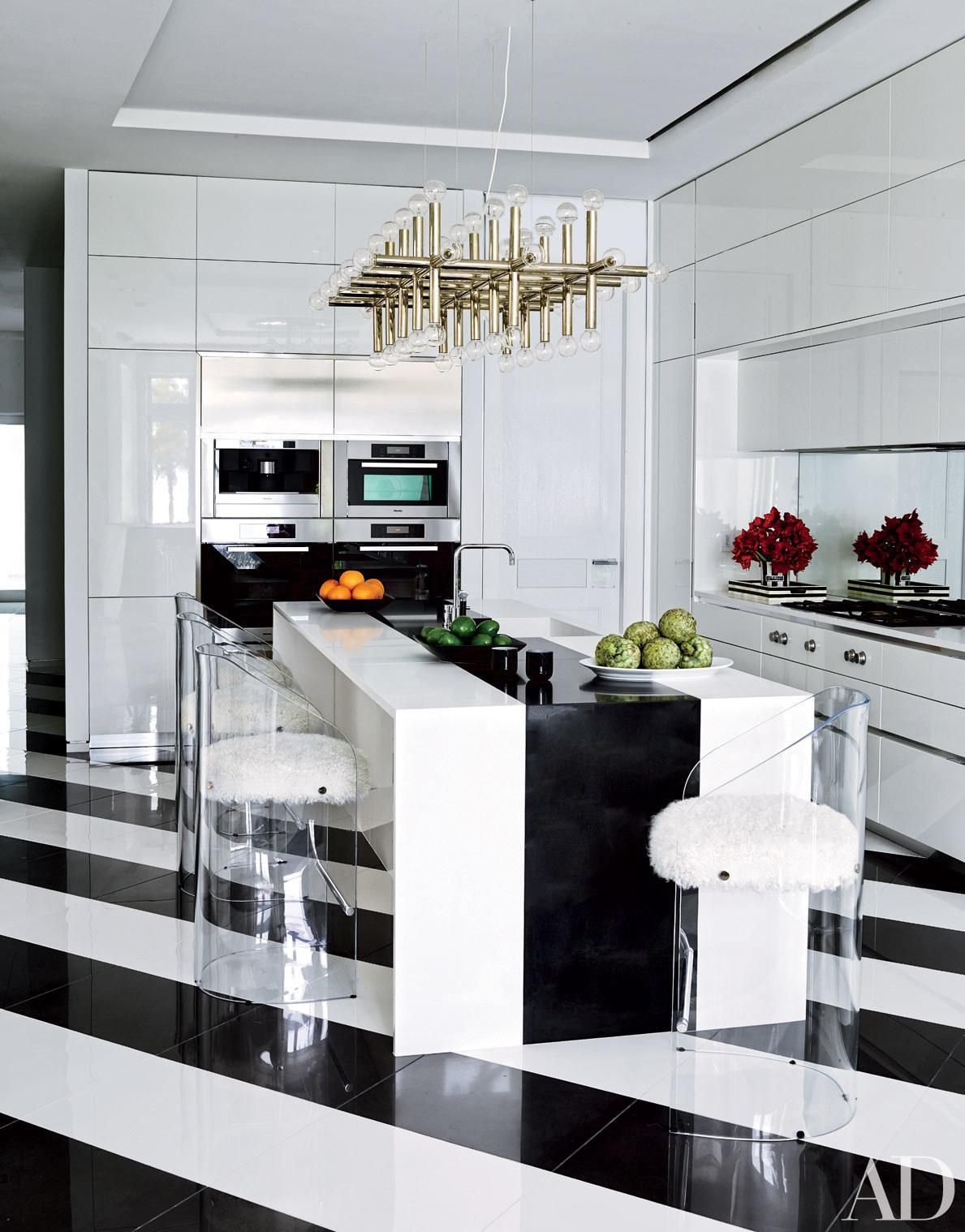 At Dee and Tommy Hilfiger's Miami-area estate, decorated with the help of Martyn Lawrence Bullard, acrylic stools, cushioned in Mongolian lamb's wool, gather around the kitchen's Caesarstone island. Read on to see more incredibly chic celebrity kitchens.