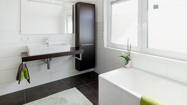 Badezimmer Dunkle Bodenfliesen Weiße Wandfliesen Badewanne Waschtisch  Spiegel Wandschrank Heller Teppich Fenster