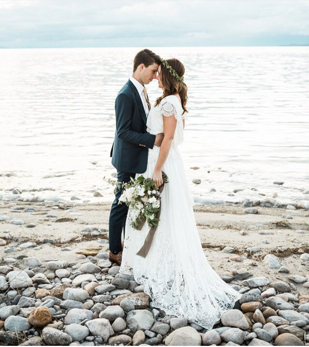 Modest wedding dress with draped sleeve and a tiered boho skirt from