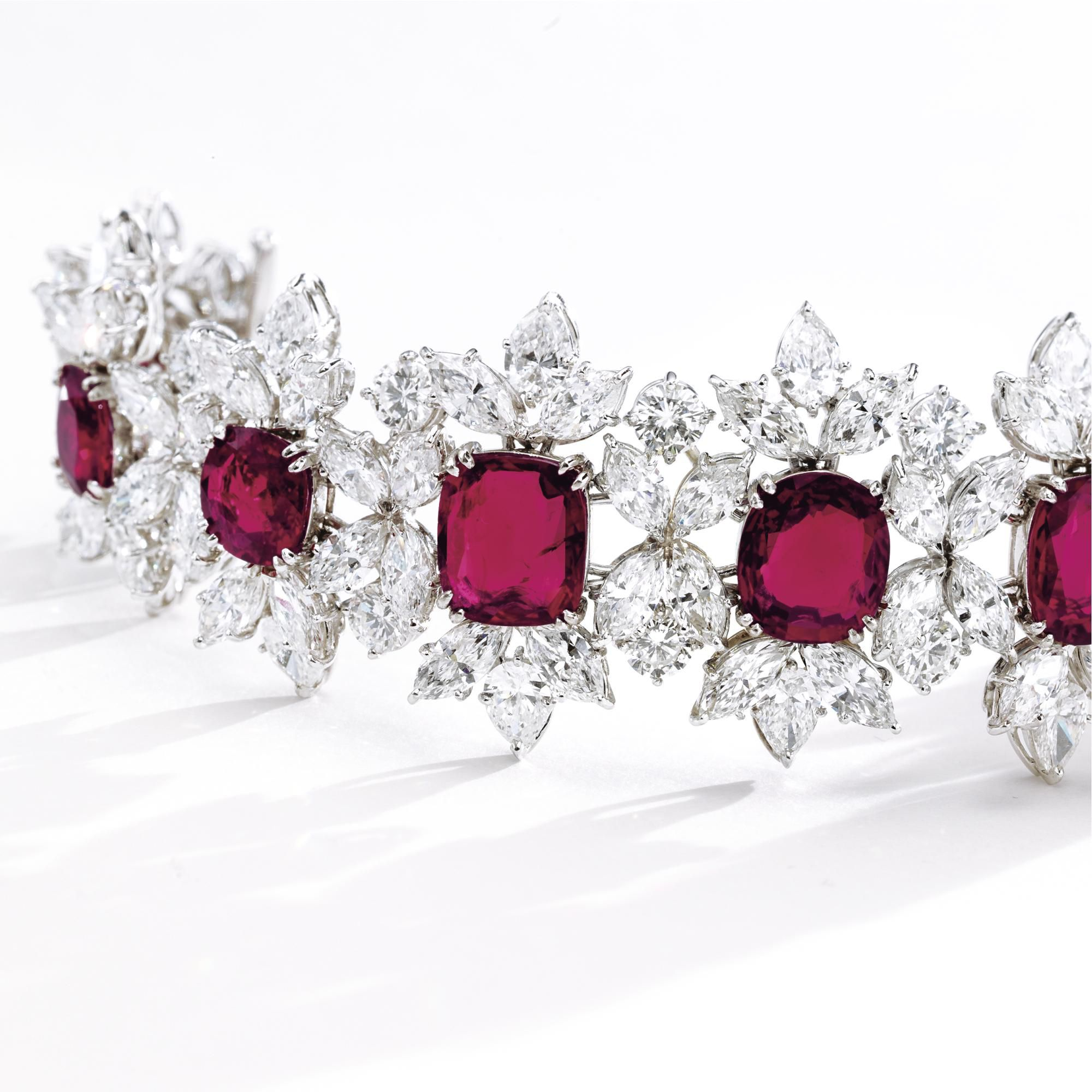 RUBY AND DIAMOND BRACELET, HARRY WINSTON, CIRCA 1960 Designed as a series of floral clusters slightly graduating in size from the center, set with 10 cushion-shaped rubies weighing approximately 30.28 carats, framed by 20 pear-shaped, 80 marquise-shaped and 20 round diamonds weighing a total of approximately 43.00 carats, mounted in platinum, length 7¼ inches, signed Winston and HW.