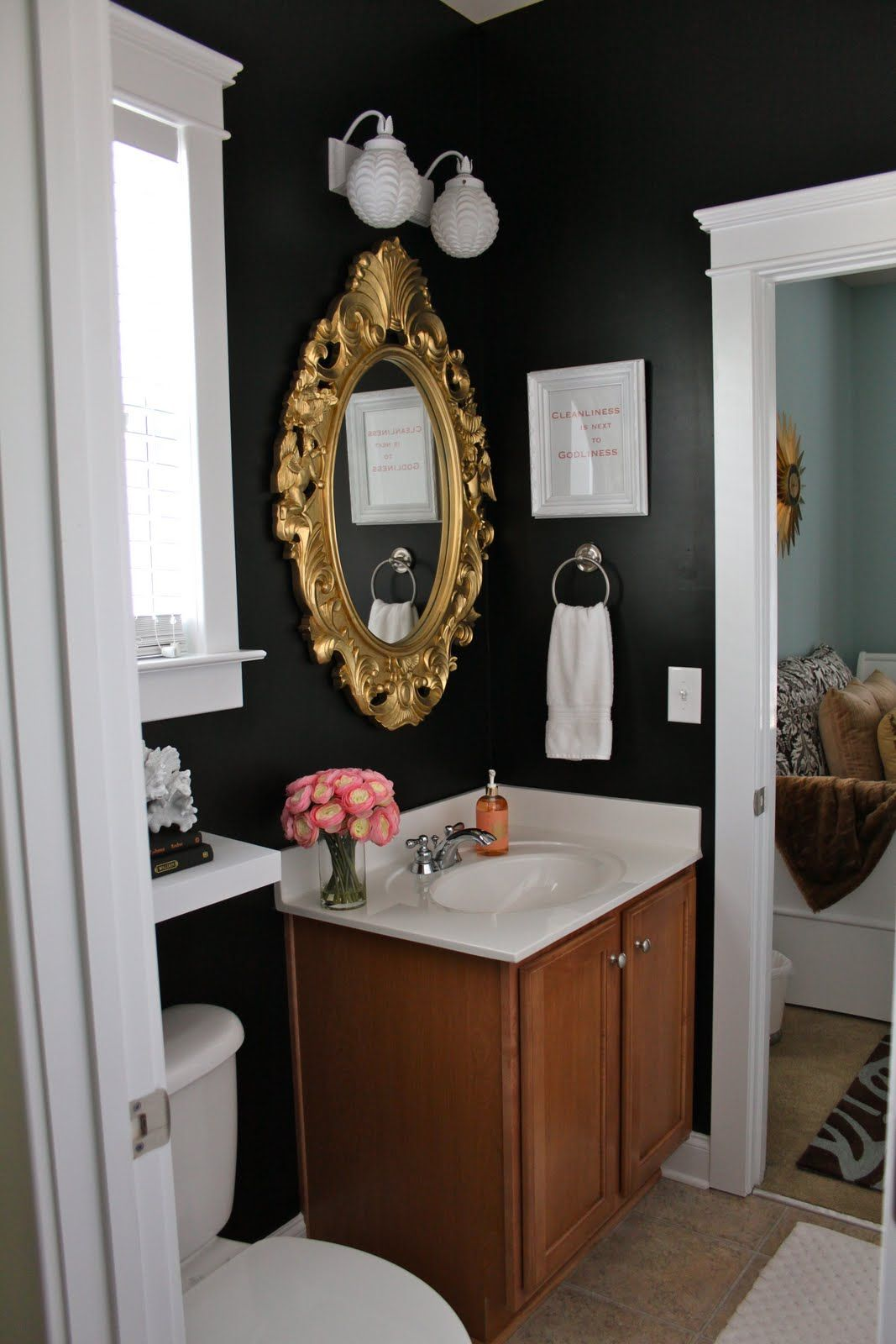 Black Walls In The Bathroom With Gold Framed Mirror