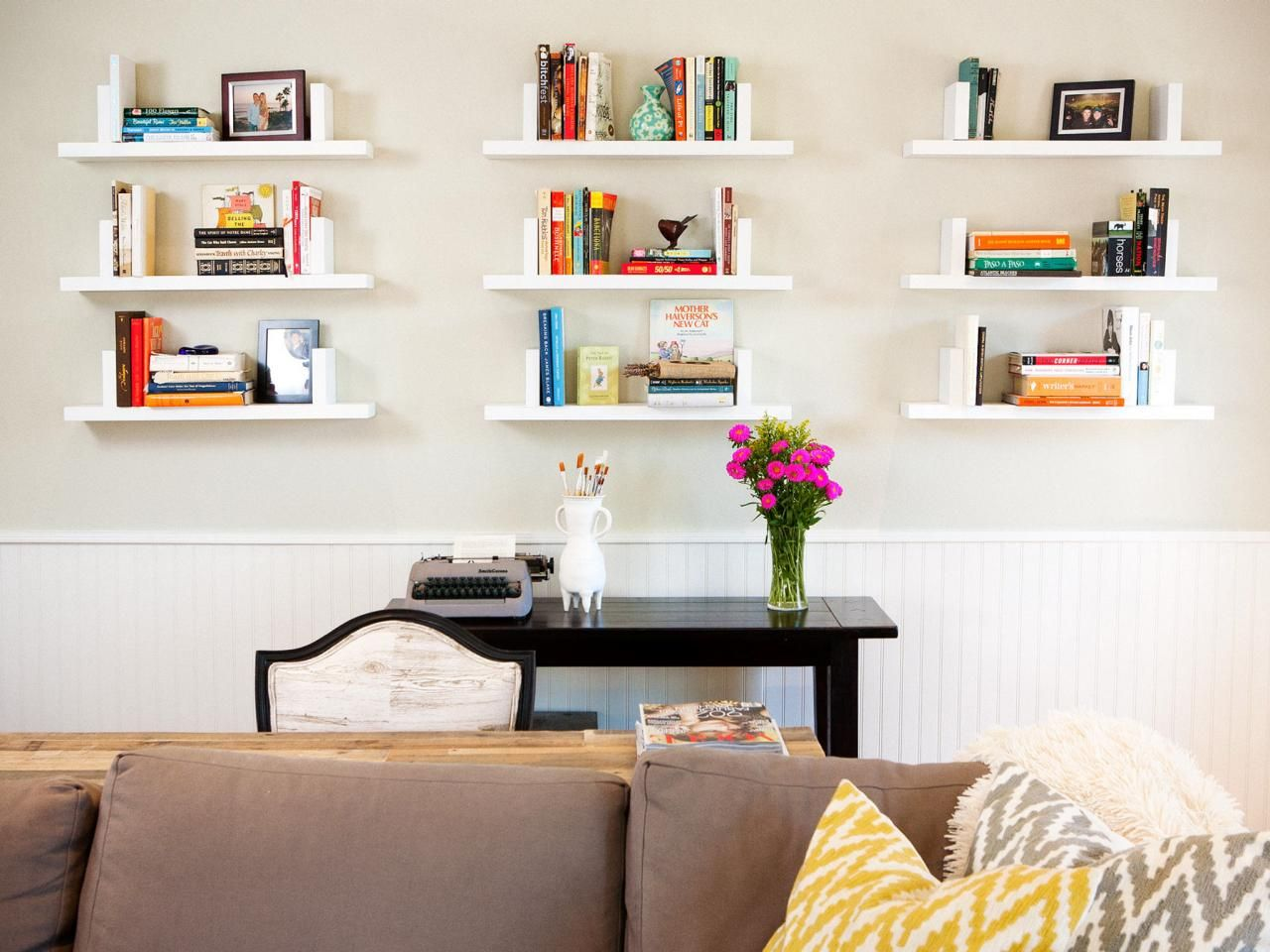 White Floating Shelves Display Books And Photos In This Transitional Living Room Hung Above