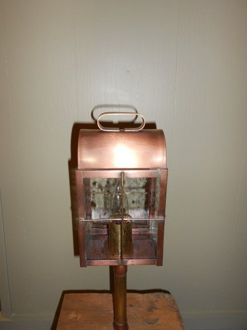 """New England Ship's Lantern Path Light in antique copper and shown with clear-seedy glass. Available in other finishes and glass options. (Priced with clear glass) Size:5-1/4""""W x 4-1/2""""D x 16""""H.    New England Ship's lantern was used in the early 18th and 19th centuries. The double-roofed chimney was an efficient ventilator that kept drafts and wind from extinguishing the candles. Today, this lantern remains a classic early lantern and is a worthy choice for practically any house or building."""