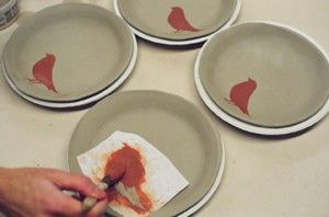 Making a set of plates with slab template using paper plates. Photo of Amanda Wilton-Green decorating slab plates using a stencil