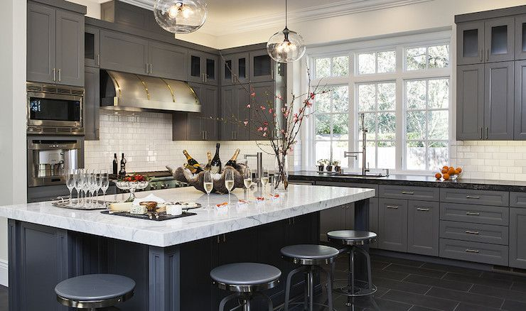 Gorgeous kitchen features gray cabinets paired with black leathered