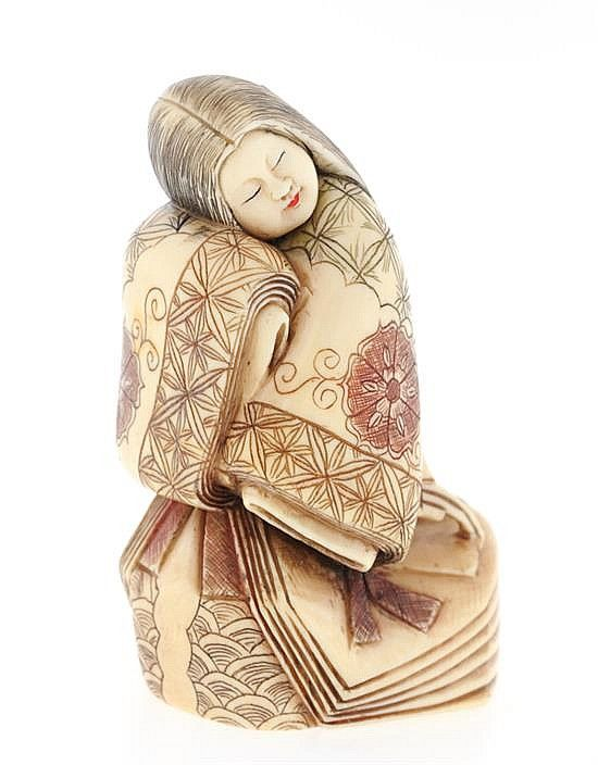A JAPANESE CARVED IVORY OKIMONO The carved ivory okimono depicting a robed geisha with scrimshawed and polychrome decoration. 2 1/2 x 2 x 1 1/2 inches.