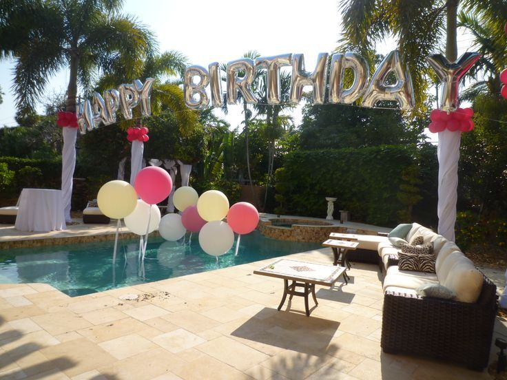 Birthday balloon arch over a swimming pool. Backyard party