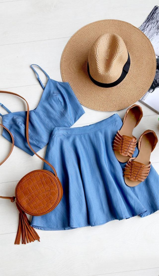casual outfit inspiration, summer style, brimmed sun hat, brown leather sandals, two piece romper, blue crop top, blue mini skirt, brown tassel bag