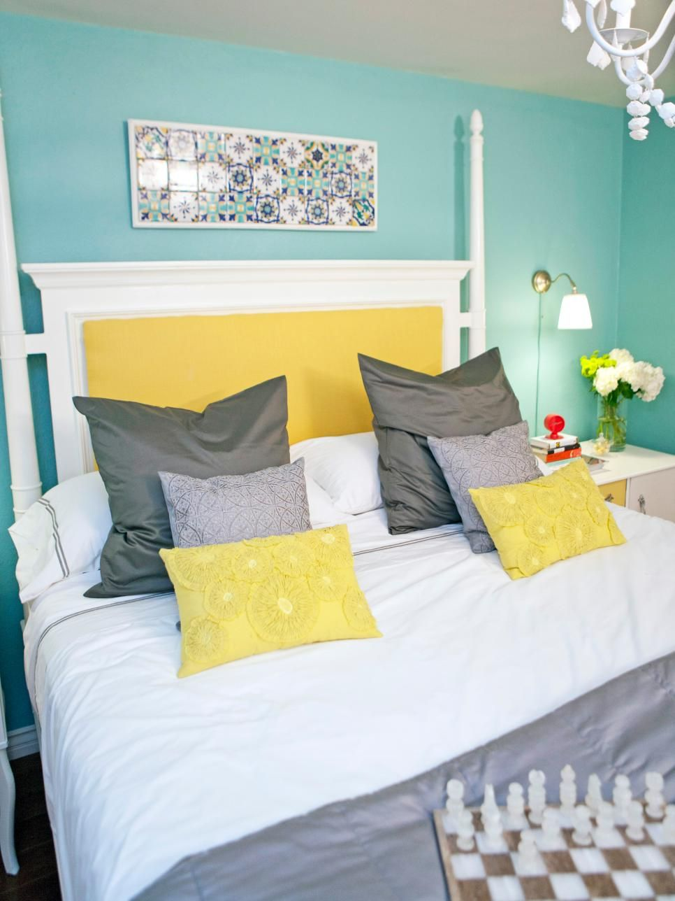 A bright white and yellow four-poster bed pops against the robins ...