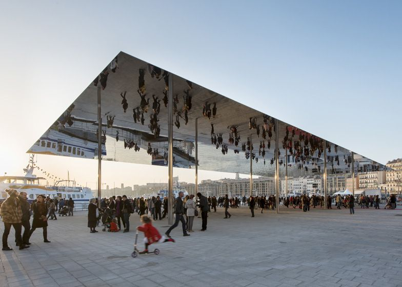 A Polished Steel Canopy Reflects Visitors Walking Underneath At