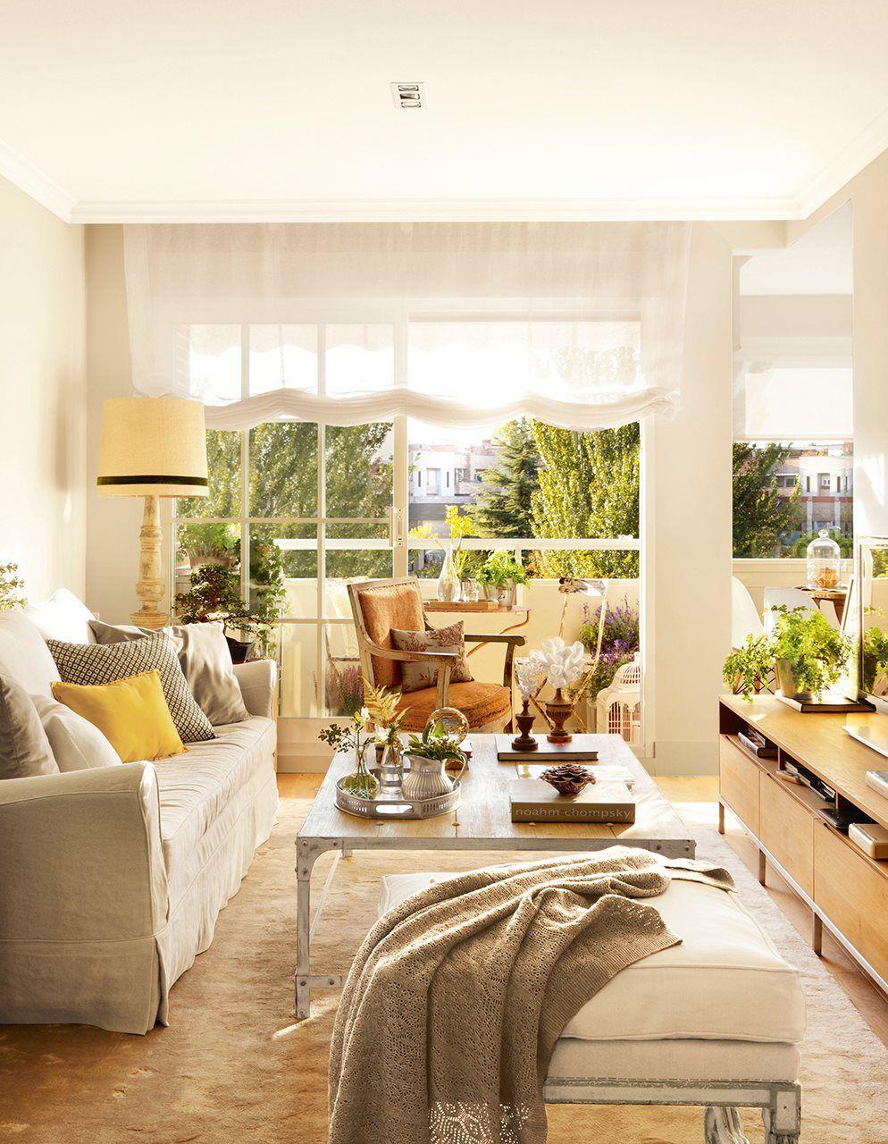 Salón con grandes ventanales con estores blancos, sofá con funda ...