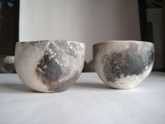A pair of cups made from white earthenware, pinched and smoothed into shape, polished with leather and a worn beach stone, lined with a translucent crackle glaze and fired in a primitive pit filled with salvaged hardwood. The smoldering fire gives the cup its unique color and depth and reveals all the processes that went into its making.