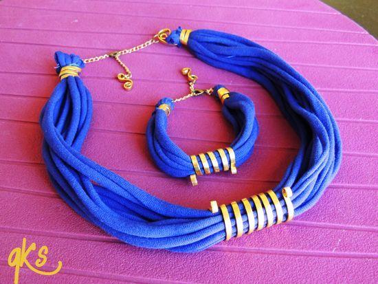 conjunto de collar y pulsera hechos con tela, con detalle central de alambre plano, cierre del mismo alambre, cierre con cadena dorada y detalle colgante, color violeta y dorado....: