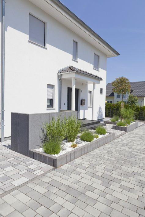 Die Beete im Vorgarten sind von Palisaden begrenzt. Das Hydropor-Pflaster passt dazu gut und liefert mit Farbspiel eine ruhige Eingangssituation. #rinnbeton #design #gartengestaltung