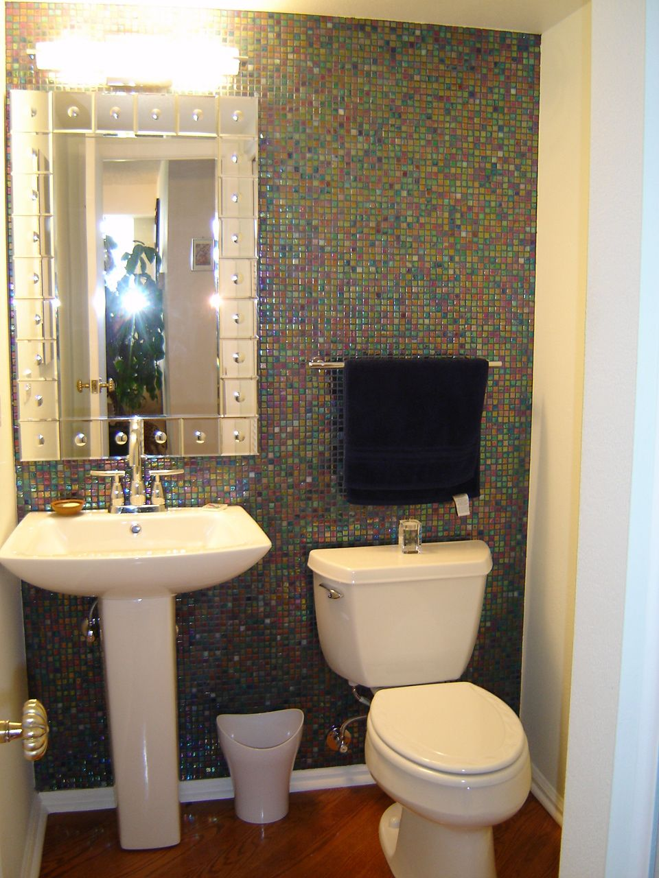Small powder room with large mirror and sconces on the side ...