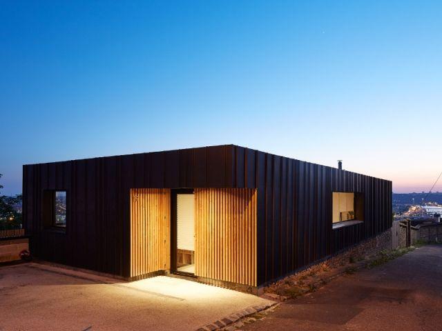 Une maison en zinc noir posée sur un mur en brique Construction