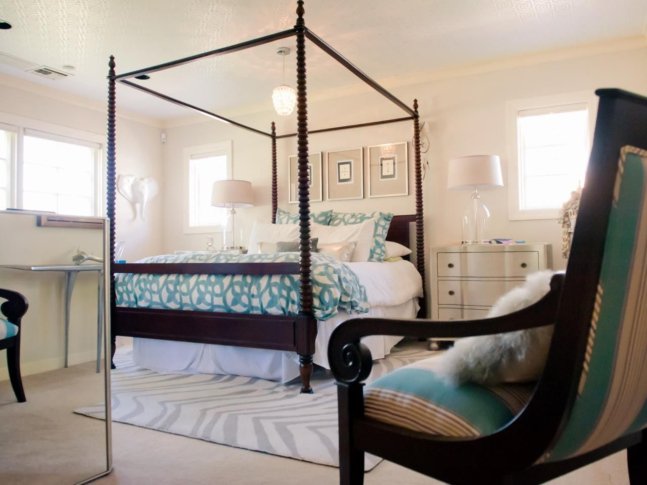 Classic black and white furnishings pair with teal accents in the bed  linens and chair upholstery. Classic black and white furnishings pair with teal accents in the
