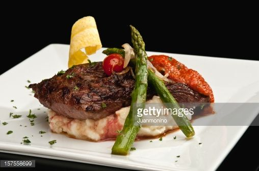 Sirloin steak with mashed potatoes and asparagus on black background ...