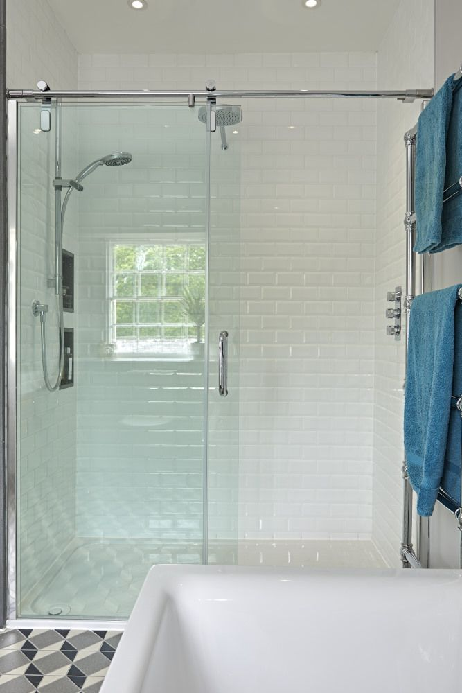 Large shower cubicle with glass shower screen, white brick tiles ...