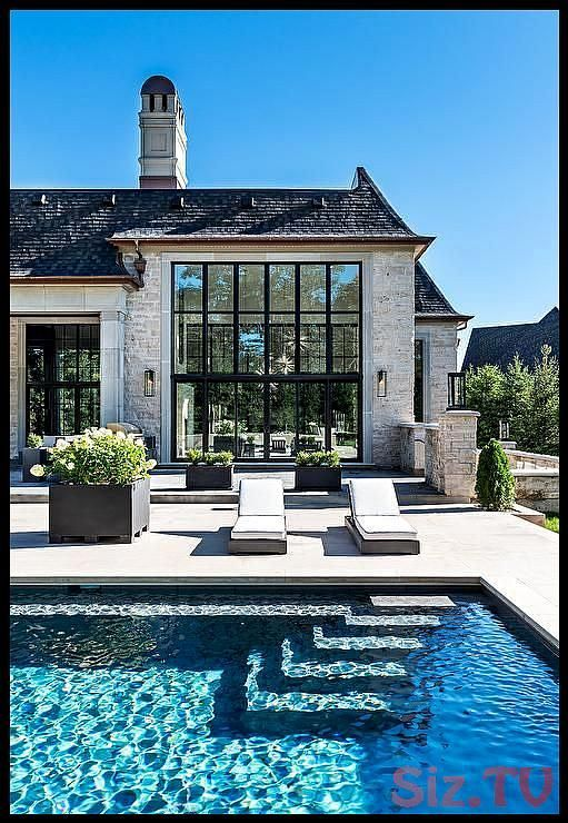 Stunning French style home with an inground rectangular pool features wicker pool loungers black planters and round fire pits Stunning French style home with an inground...