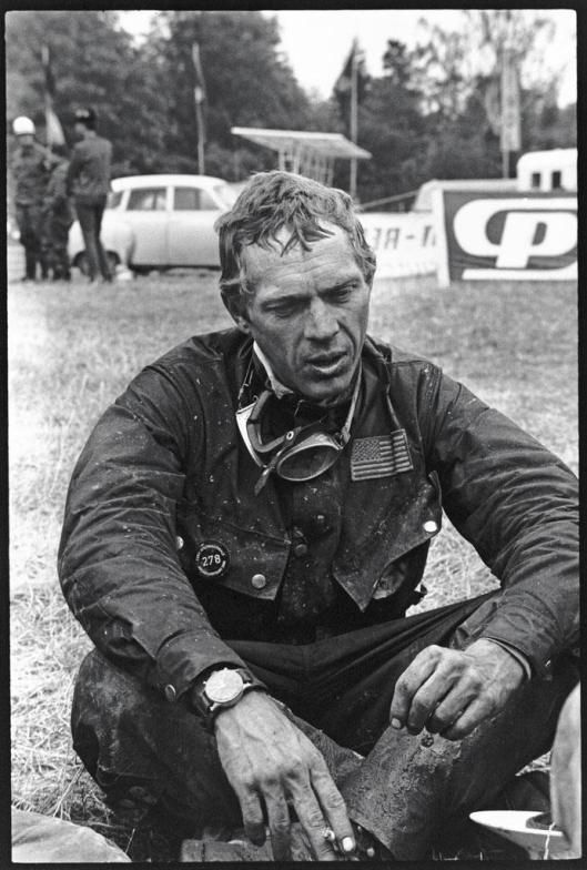 Steve McQueen seated on the ground at a rest point ISDT 1964
