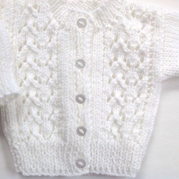 Age 0 - 6 months, this is a little infant white cardigan with a pretty lacy pattern on the front. The little cardigan is knitted in a medium weight, acrylic yarn, and has white buttons up to a crew neck and long sleeves. The perfect baby shower gift, or a Baptism cardigan. Measurements