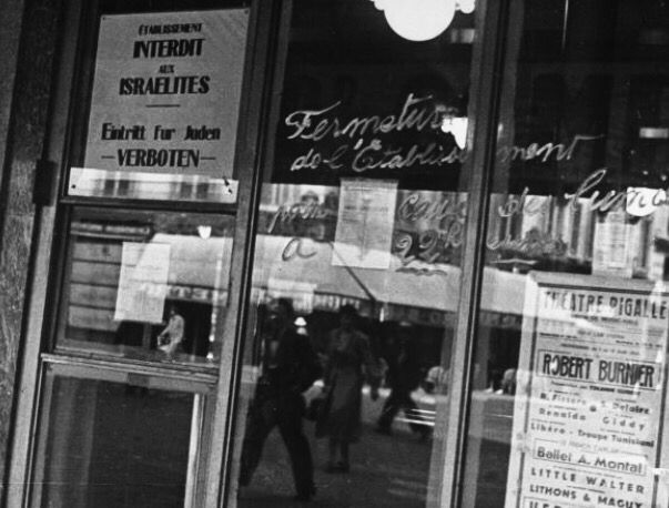 Business on the Champs Elyssees in German-occupeid France with signs saying Jews not wanted or Jews Forbidden to enter.