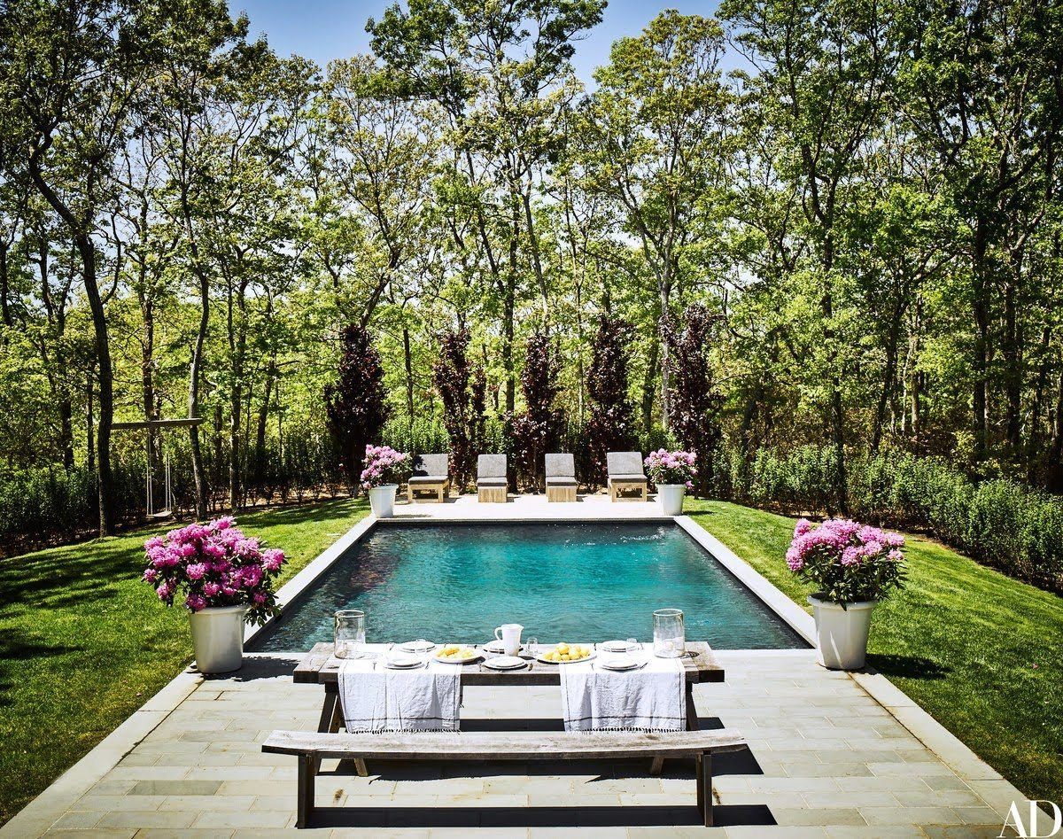 """""""In the Hamptons, the grounds are so vast and overwhelming. But this property has a nice coziness, which we really, really love,"""" says Romanek. The large white planters, wood picnic table and chaise lounge chairs around the pool area are from Bloom in Sag Harbor."""