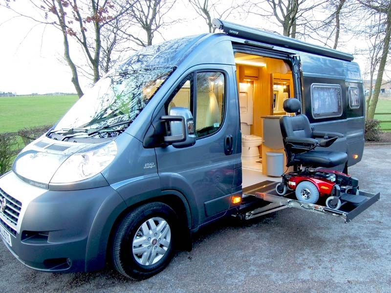 A power chair being lifted by the side access to a motorhome