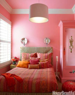 This pink bedroom in San Francisco, California by designer Stephen Shubel incorporates a range of pinks with pops of orange. The neutral colored headboard and carpet balance out the juicy color scheme. Walls are Benjamin Moore's Tickled Pink.
