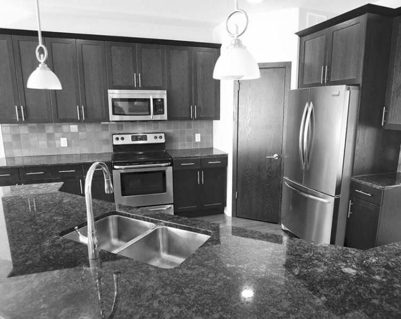 Exceptionnel Winnipeg Free Press/The Kitchen Features Grey Granite Countertops And Dark  Maple Cabinets.