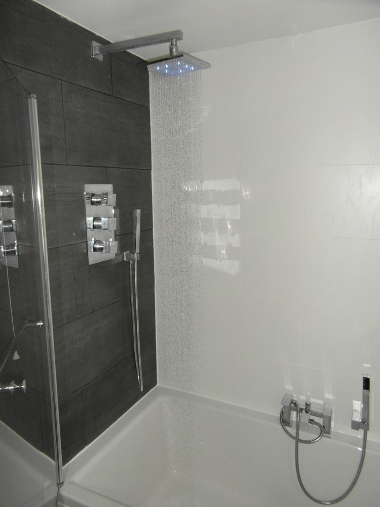 Overhead shower in conventional bathroom with bathtub. Make your home design  dreams come true.