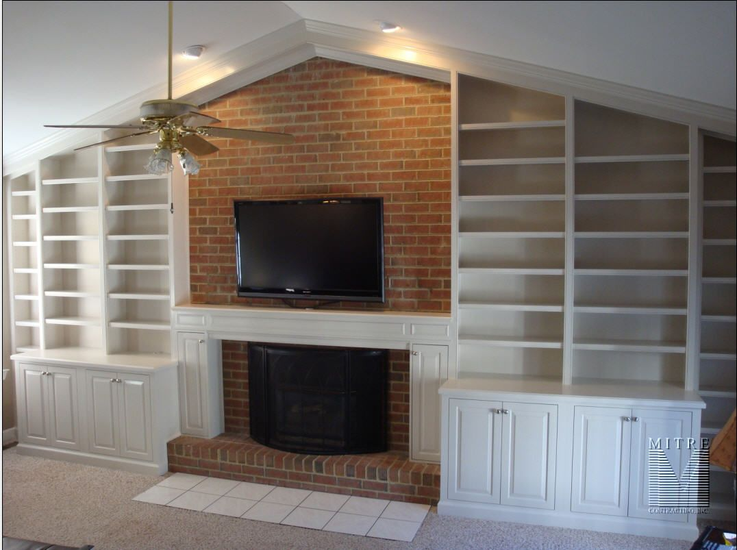 Builtin cabinetry surrounding fireplace with boxed mantel the