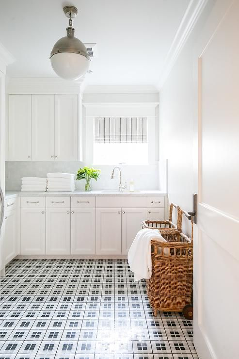 Modern Farmhouse Laundry Room: Black and white floor tiles accent white shaker cabinets with polished nickel knobs and pulls and a gray marble countertop. #whiteshakercabinets